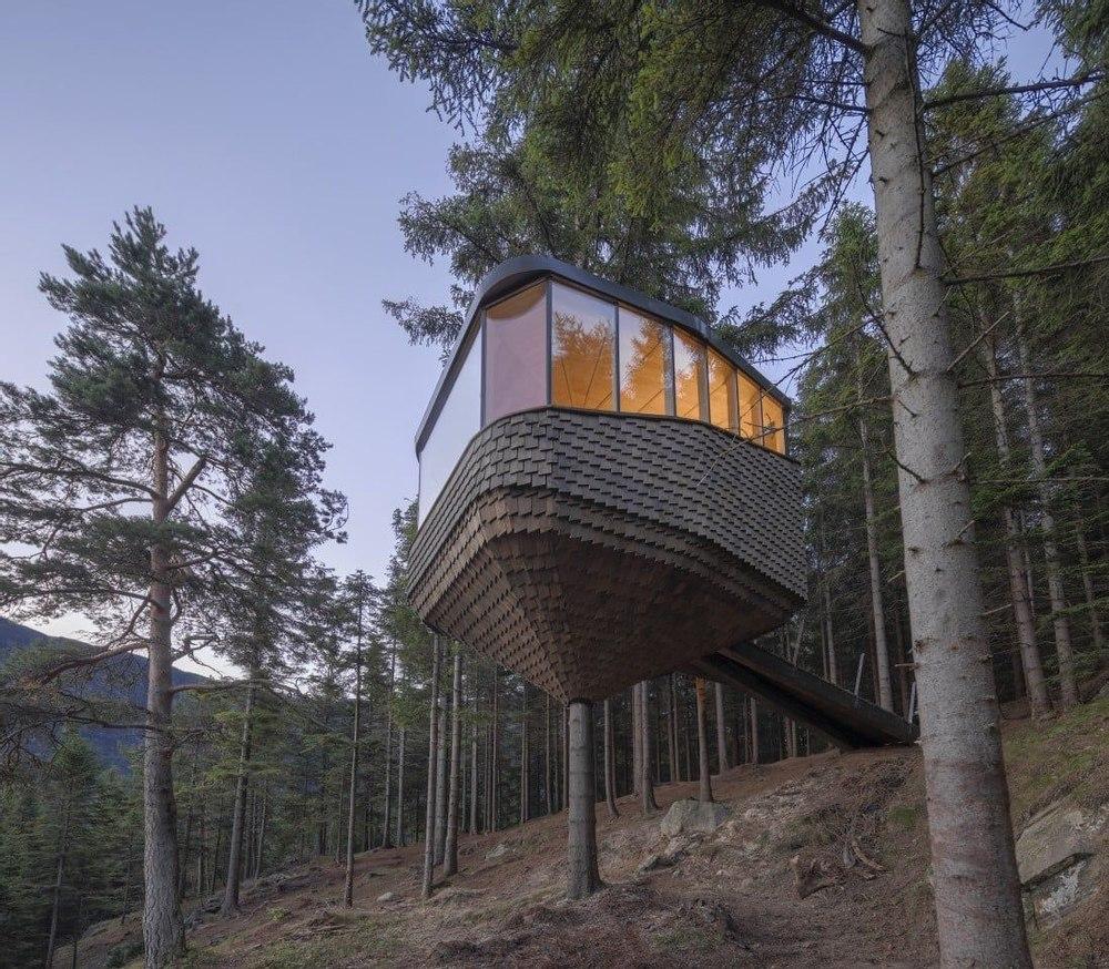 Окруженный деревьями роскошный домик на дереве с видом на норвежский фьорд