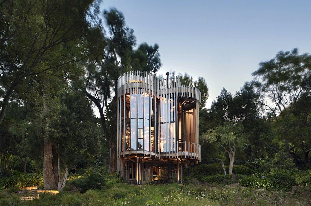Современный дизайн домика в лесу, состоящего из цилиндрических башен, органично сливается с окружающей природой